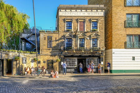 Wapping, London, UK - May 7, 2018: Horizontal shot of the Prospect of Whitby Pub in Wapping with people enjoying the sunshine outside. Afternoon shot with lovely light.