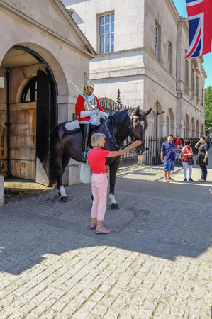Whitehall, London, UK - June 8, 2018: Mounted Royal Guard on duty i Whitehall with a lady tourist patting the horse.