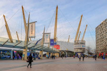 Greenwich, London, UK - February 14, 2018: The O2 dome with its surrounding shops and restaurants.  People strolling along the walkway. Editorial