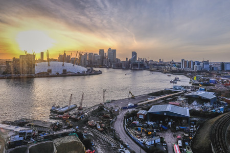 Roya Victoria Dock, London, uk - February 14, 2018: Aeirial view from the cable car at sunset.  Shows the sun going down behind the O2 and Canary Wharf as you make the crossing.