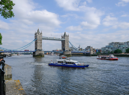 South Bank, London, UK - June 8, 2018: View of Tower Bridge on the  Thames on a sunny summer afternoon.  Taken from the viewing point near the Tower and shows a clipper and cruiser. Redakční