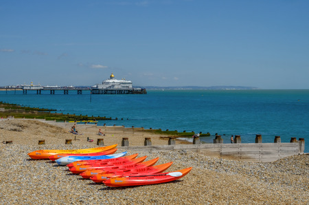 Eastbourne, Sussex, UK - August 1, 2018: row of bright coloured kayaks on a shingle beach with pier in the backbground.  Taken on a blue sky sunny summer's day. Standard-Bild - 118865497