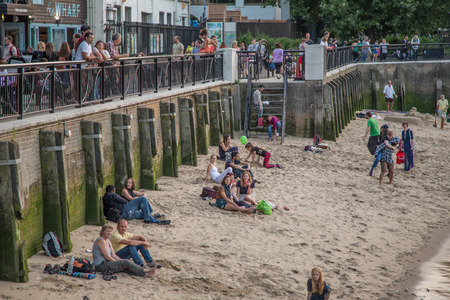 South Bank, Southwark, London, UK - August 6, 2014:  Sandy beach at the side of the River Thames on South Bank with people enjoying the late evening sunshine.