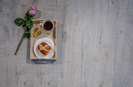 Flatbed top shot of a tray with lemon tea and hot cross bun.  A beautiful single pink rose stem lying beside.  Situated on a third with copyspace beside.