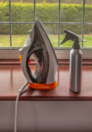 Hand held electric modern steam iron standing on a wooden windowsill with a silver colored spray bottle beside it.
