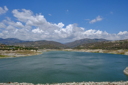 Scenic landscape shot of Germasogeia dam in Cyprus on a beautiful blue sky day.  Wind patterns on the water and clouds over the mountains in the background.