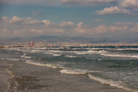 Landscape view of Limassol with mountains in the background and Limassol docks in the middle with waves and beach in the foreground.