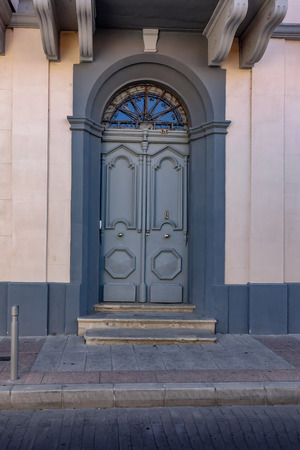 Grand arched wooden door. Traditional style found in Cypriot cities. Painted grey with a pale pink wall.