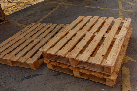 Three wooden pallets stacked on the floor which has yellow markings.