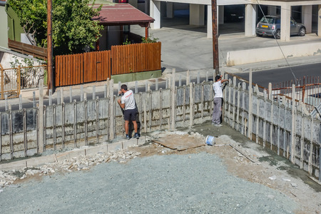 Limassol, Cyprus - April 3, 2018: Two builders dismantling the shuttering on a concrete wall that is newly constructed.
