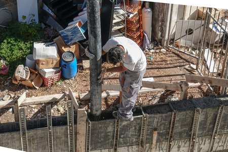 Limassol, Cyprus - April 3, 2018:  Man standing on shuttered wall holding the chute and pouring cement into the shuttering.   Aerial shot looking down a the builder.