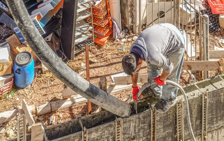 Limassol, Cyprus - April 3, 2018:  Man standing on shuttered wall bending over and pouring cement into the shuttering.   Aerial shot looking down a the builder.