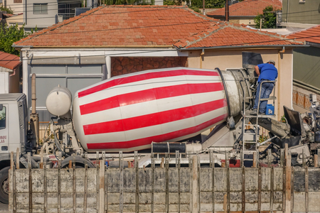Limassol, Cyprus - April 3, 2018:  Red and white striped cement mixer truck with a man working at the rear