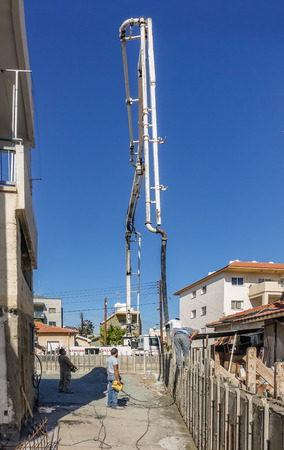 Limassol, Cyprus - April 3, 2018: Delivery of concrete to make a shutter prepared wall.  Long telescopic arm reaching high into the sky to pump cement a long way from the mixer truck. 報道画像