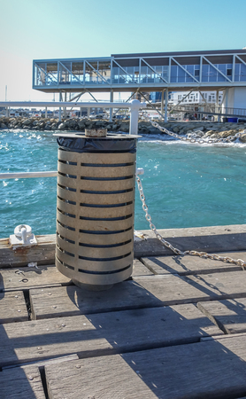 Limassol Port, Limassol, Cyprus - October 31, 2018: Modern rubbish bin with water and new restaurants in the background.