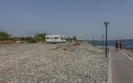 St. Barbara, Limassol, Cyprus - November 2, 2018: Camper van parked up besidethe prommendade at the sea front.  Two joggers on the path.