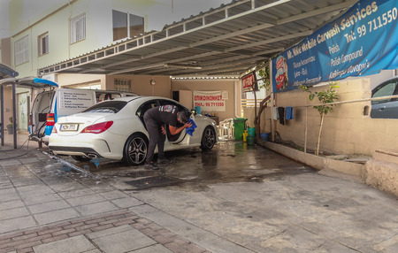 Limassol, Cyprus - November 7, 2018: Man wiping a white car dry after giving it a car wash.
