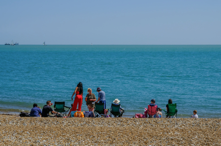 Eastbourne, Sussex, England, UK - August 1, 2018: Families picnicing on the beach in Eastbourne.  Taken on a sunny blue sky summers afternoon and shows rear view of people sitting and standing nearthe waters edge. Sajtókép