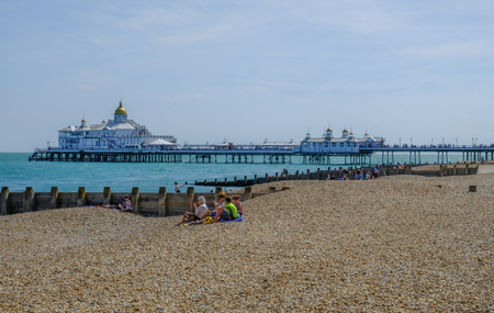 Eastbourne, Sussex, England, UK - August 1, 2018: View from the beach of the pier.  Family picnicing on the beach in the foreground.  Shot taken on a bright sunny summers afternoon. Sajtókép