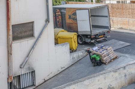 Limassol, Cyprus n- November 4, 2018: Delivery of bags of flour to a bakery. Bags are piled up on a pallet and being taken into the building down a steep slope. Redakční