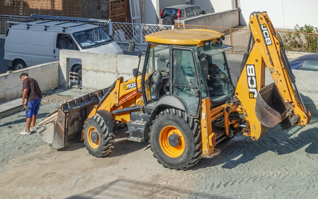 Limassol, Cyprus - November 4, 2018: Large yellow JCB tractor on a building site. Vehicle is large in the frame.  Man with tape measure in front of the vehicle.