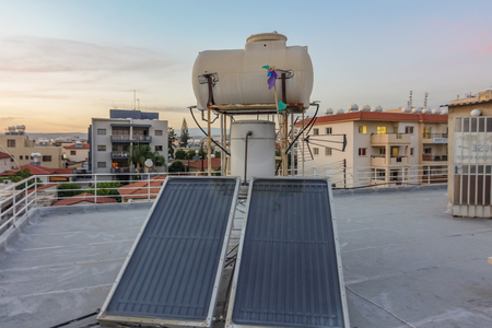 Limassol, Cyprus - April 4, 2015: Solar panelsn with water tank on the roof of building.  Taken on a sunny evening. Redactioneel