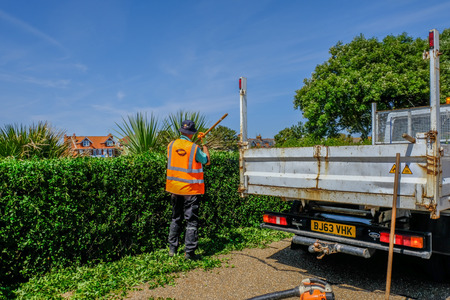 Eastbourne, Sussex, England, UK - August 1, 2018: Workmanj raking the trimmings of a newly cut edge.  Wearing a hi-viz jacketand backend of truck. Sajtókép