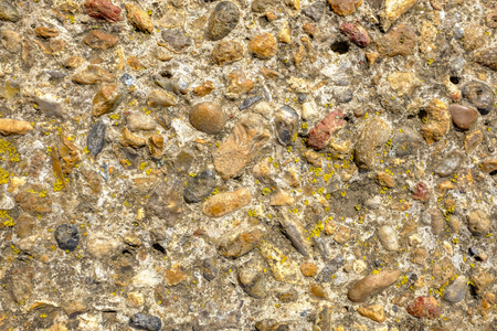 Background shot of stone wall which is weathered and has yellow lichen growing.