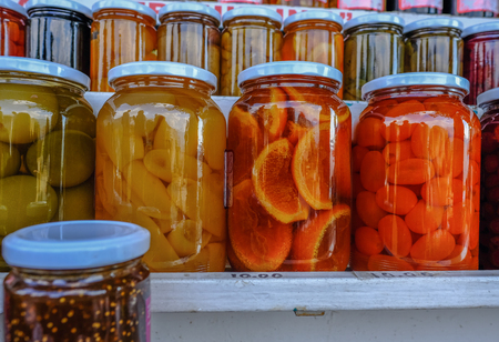 Jars of fruit preserves in rows.  Bright vibrant colours.