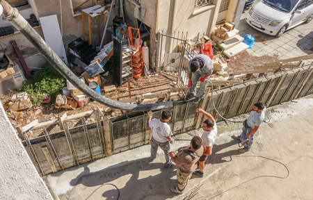 Limassol, Cyprus - April 3, 2018:  Man standing on shuttered wall holding the chute and pouring cement into the shuttering.   Aerial shot looking down on group of workers.