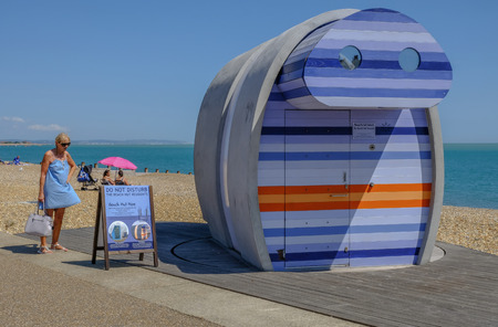 Eastbourne, Sussex, UK - August 1, 2018: Lady in blue sun dress reading information about the rentable stripy beach hut called spyglass,  on the beach in Eastbourne.