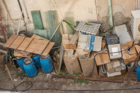 Limassol, Cyprus - November 9, 2018:  Pile of rubbish including cardboard boxes, blue cannisters and old glass shelves.