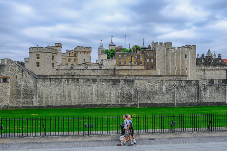 Tower of London, London, UK - June 8, 2018: Side view of the Tower of London, with a couple strolling along the walkway outside of the railings. Editorial