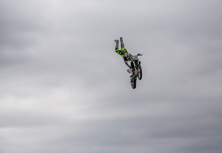 Enfield, London, UK - May 24 2015: Aerial shot of stunt rider upside down  in mid-air on his stunt bike against an overcast sky.