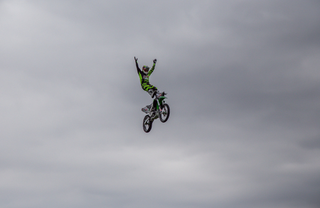 Enfield, London, UK - May 24 2015: Aerial shot of stunt rider standing up  in mid-air on stunt bike against an overcast sky.