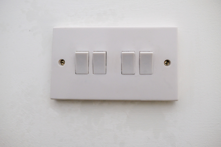 Four way electrical light switch.  White plastic switch with two screws and set agains a white painted wall.