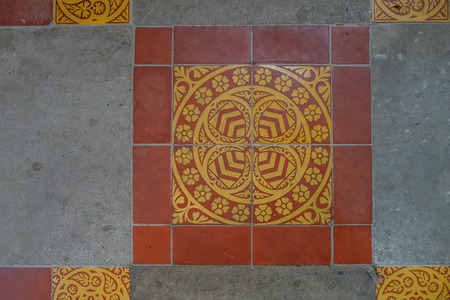 Ancient english floor tile closeup.  Beautiful traditional patterns in yellow and red surrounded by cement.  Patterns of shields and english rose in perfect symetry.