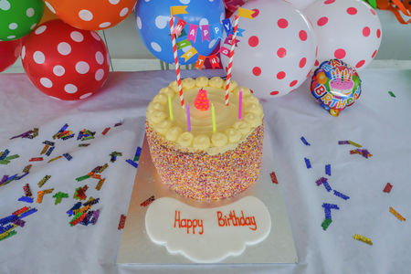 Childrens Birthday cake with candles set in front of colourful spotty ballons. Ready for a party with Happy Birthday written in the foreground.