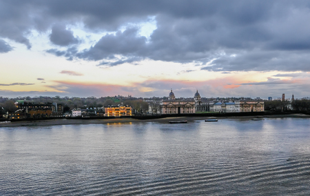 Greenwich Royal Naval College landscape, with river Thames in the foreground and beautiful sunset colours in the sky.