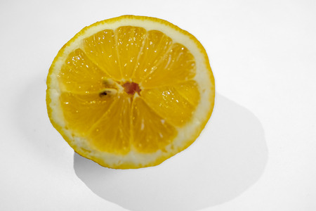 Half a yellow lemon with two pips on a white background with a shaddow of the lemon.