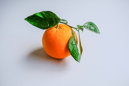 Single whole orange with its skin on, bright orange colour with fresh green leaves attached and set on a light grey background. Stock fotó