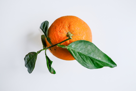 Natural single orange with green leaves on a plain light grey background. Stock fotó