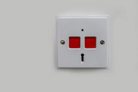 White plastic panic panel with two red square push buttons and a key hole to reset.  Push here in an emergency. Stock fotó