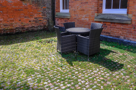 Wicker table and arm chairs  in dark grey set in an old courtyard witha red brick background.  Weeds and moss between the cobbles add to a traditioanal feel.