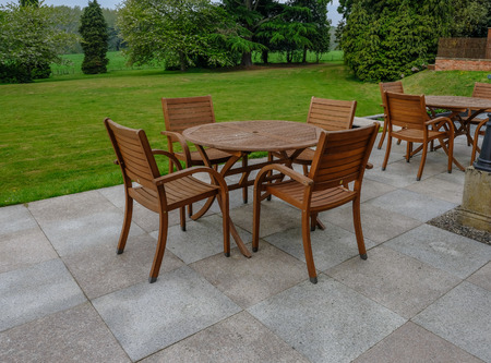Wooden table and chairs set on a slabbed patio area with beautiful lawned and tree view.