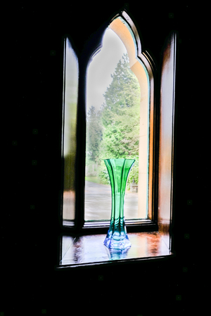 Green glass vase in an ancient window on the sill and trees seen through the window.  Polished wooden sill and an interesting shape of the window.