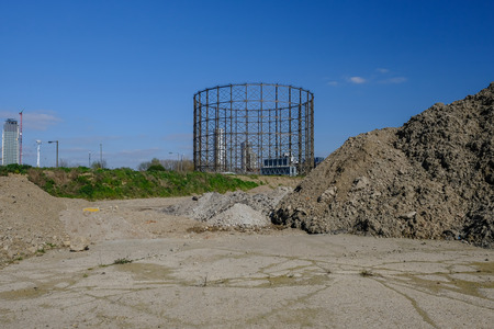 Pile of earth with a concrete base in the foreground and an old gasworks in the background.  Site being prepared for future construction.