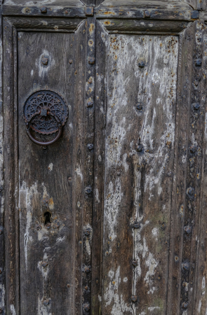 Ancient wooden door. Door has lovely black metal patterned clasp and studded pattern.  Shows great texture in the old wood and a large keyhole cut into the wood.  This is a closeup section of the door.