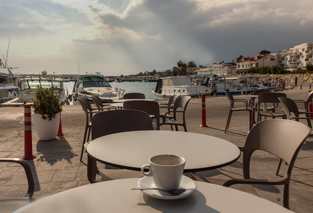 Sitting at a table at the marina cafe in Zygi with an empty coffee cup and great view of the habour.