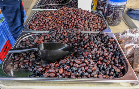 Metal containers full of black olives on a stall at a street market. Black scoop for serving these dried black olives.